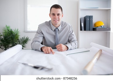 Smiling architect pointing at a plan
