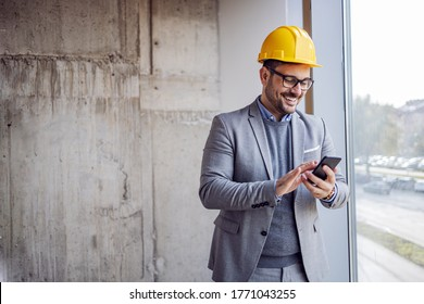 Smiling architect in suit and with helmet on head standing in building in construction process next to window and typing message on smart phone.