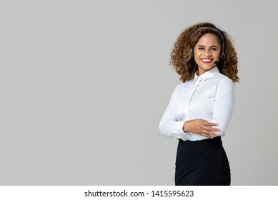 Smiling arms crossed African American woman wearing microphone headset as a call center staff studio shot on light gray background with copy space