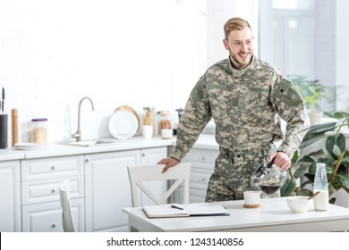 smiling army soldier pouring coffee in kitchen