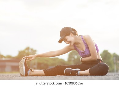 Smiling of Asia woman athlete sitting on an exercise mat and stretching in a field.