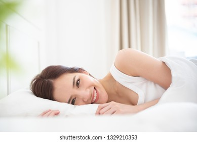 Smiling Asian beautiful woman waking up on her bed at her bedroom on the holiday. Looking to camera.
