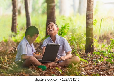 Smiling Asian boys using a laptop for education Choose focus on the eyes with a blurred background.