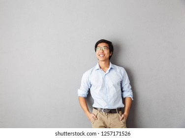 Smiling asian business man standing isolated over gray background, looking away
