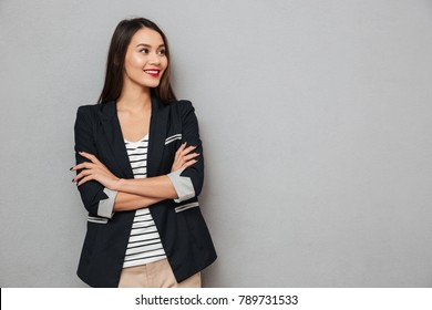 Smiling asian business woman with crossed arms looking away over gray background