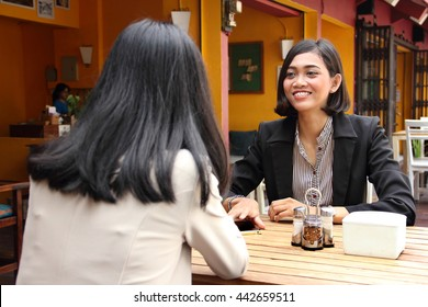Smiling Asian business woman having a conversation with her female associate in a restaurant table