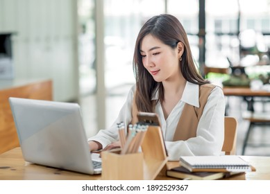 Smiling asian business woman sitting in a modern office.