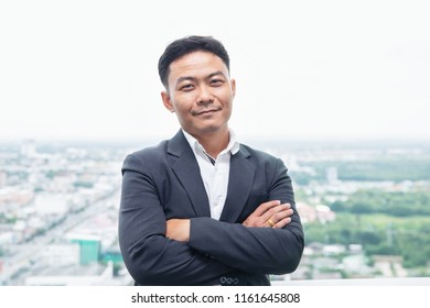 smiling asian businessman with arm crossing on skyscraper background