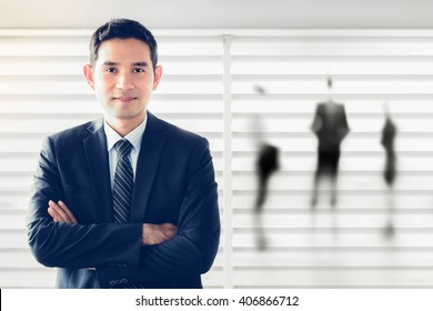 Smiling Asian businessman crossing his arms - leader and success businessman concept