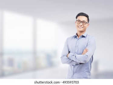 Smiling Asian businessman in glasses standing with arms folded against blurred office background. Concept of successful startup founder. Mock up