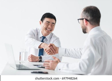 smiling asian businessman shaking hands with colleague at workplace isolated on white