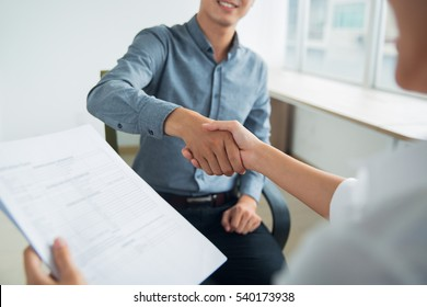 Smiling Asian businessman shaking partners hand