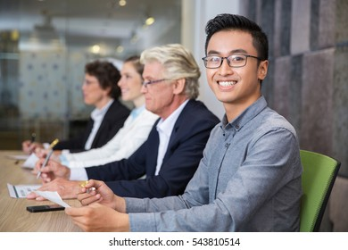 Smiling Asian businessman sitting at conference