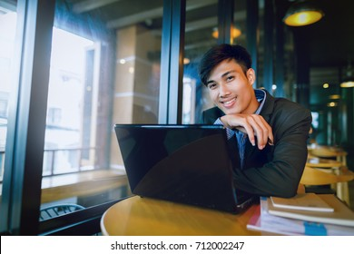 Smiling asian businessman in suit looking at camera in the meeting room
