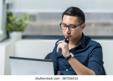 Smiling Asian Businessman Working in Front of a Computer in the Office