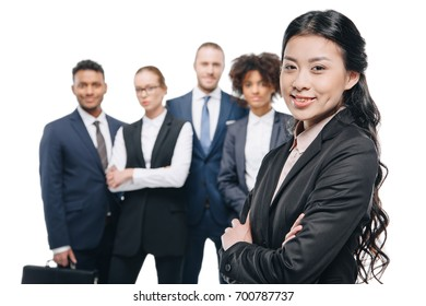 smiling asian businesswoman in formal wear with colleagues behind, isolated on white