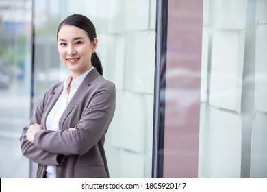Smiling Asian businesswoman on blur office building background.