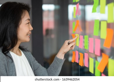 Smiling Asian businesswoman reading information, tasks or ideas on sticky papers close up, pointing at colorful post it note on glass wall, female leader planning corporate project on scrum board