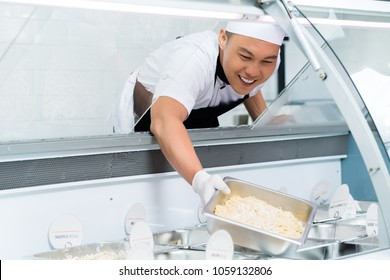 Smiling Asian chef filling a glass display counter with prepared food in metal tray leaning forwards with copy space alongside