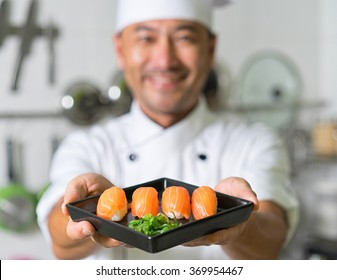 Smiling asian chef with sushi. Focus on sushi