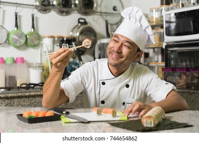 Smiling asian chef with sushi and rolls on kitchen. Focus on the face.