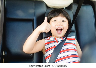 Smiling asian child girl thumbs up for good drive good trip and safe on the road. Sitting and buckle up in the car in the seat for children.