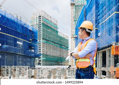 Smiling Asian construction worker with blueprint in his hand turning back and looking at building under construction