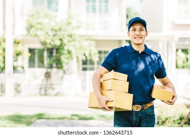 Smiling Asian delivery man with parcel box in his hand