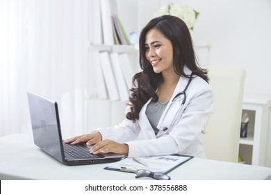 smiling asian female doctor working in office