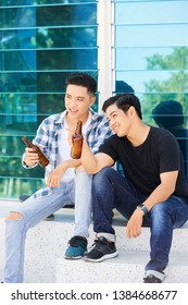 Smiling Asian friends sitting in the city discussing something and drinking beer