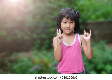 Smiling Asian girl (age 6) with the firth missing teeth in mount and showing her hand symbol of victory and love sign language
