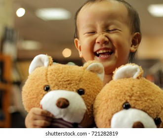 a smiling Asian girl holding bear in a clothing store