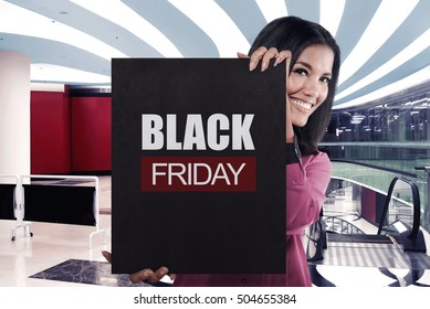 Smiling asian girl holding black banner sale with BLACK FRIDAY message on the mall