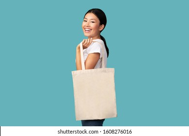Smiling Asian Girl Holding White Eco Tote Bag Smiling Standing Over Turquoise Studio Background. Ecology And Eco-Friendly Lifestyle Concept.