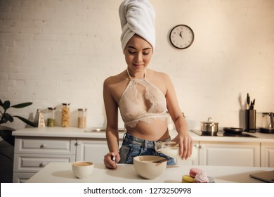 smiling asian girl in lace bralette and towel on head pouring milk into bowl with corn flakes