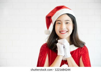 Smiling Asian Girl in red Santa Claus hat and dress standing and looking to camera over white background. Make a wishes concept. copy space. Christmas.