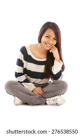 Smiling asian girl sitting on the floor over white isolated background