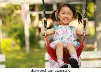 a smiling Asian girl swing on the green grass park. background for children's day