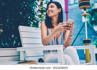 Smiling asian girl  using smartphone for browsing information sitting on cafe terrace during leisure,cheerful female in trendy wear sending and texting messages chatting with friends in networks