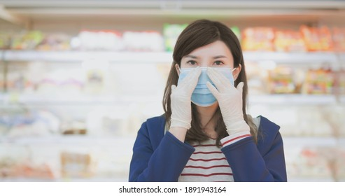 smiling asian homemaker is wearing face mask on with gloves at grocery store during virus epidemic outbreak - look to you