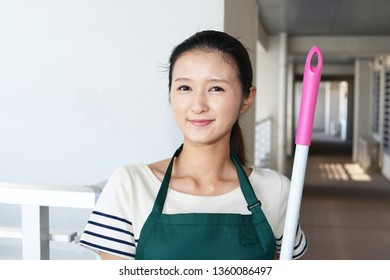Smiling Asian housewife with a broom.