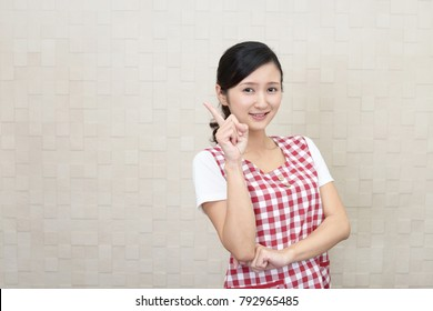 Smiling Asian housewife pointing.
