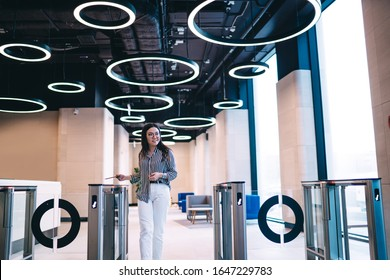 Smiling Asian joyful trendy female employee using office pass for going through electronic gate in corporate design hall looking away