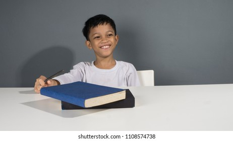 Smiling asian kid doing homework at his study table. Smiling and getting idea