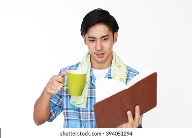 Smiling Asian man drinking coffee.