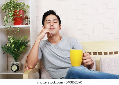 Smiling Asian man drinking coffee.
