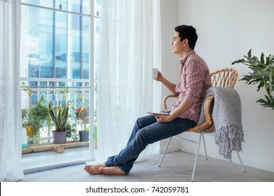 Smiling asian man drinking coffee relaxing on the couch at home