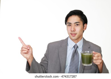 Smiling Asian man drinking a glass of juice.