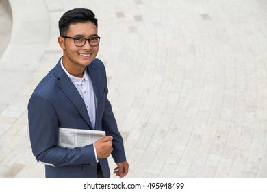 Smiling Asian man holding newspaper and walking in the stoned square. Concept of successful businessman portrait. Mock up