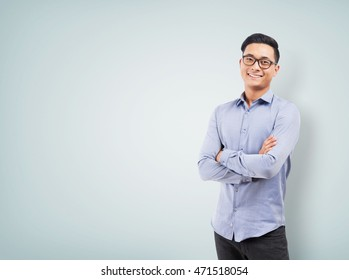 Smiling Asian man in pants and shirt standing near blank wall. Concept of businessman. Mock up